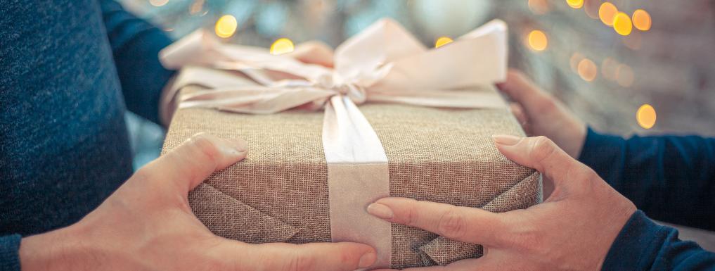 muške i ženske ruke drže poklon za novu godinu